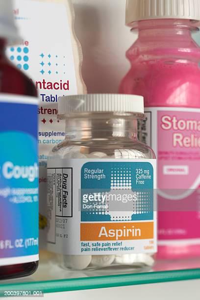Assorted medications on glass shelf (focus on bottle of aspirin)