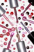 Assorted nail varnish lids with brushes and droplets, elevated view