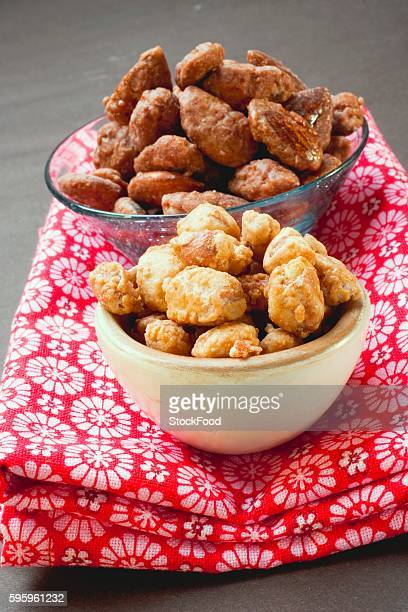 Assorted nuts to nibble in bowls on patterned cloth