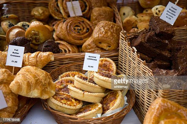 assorted pastries for sale displayed in wicker baskets