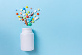 Assorted pharmaceutical medicine pills, tablets and capsules and bottle on blue background. Copy space for text.