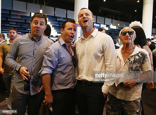Assorted punters cheer on their horse in the betting ring at The Star Epsom Day at Royal Randwick Racecourse on October 4 2014 in Sydney Australia