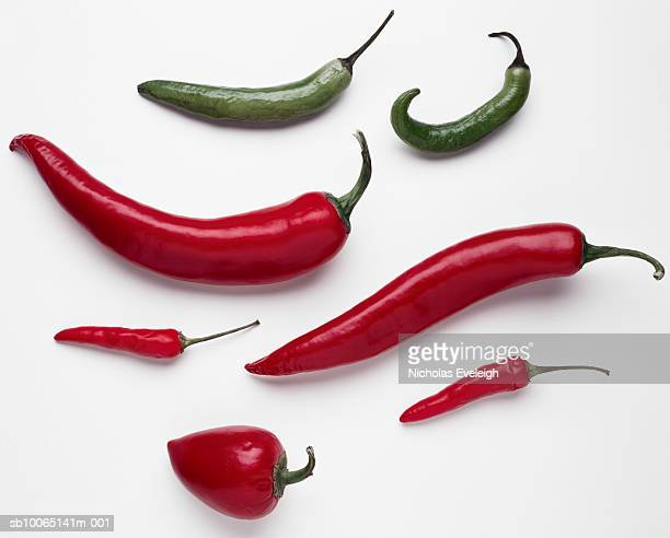 Assorted red and green hot peppers on white background