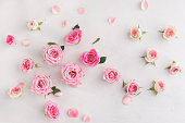 Various soft roses and leaves scattered on a vintage background, overhead view