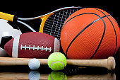 A group of assorted sports equipment on a black background including a tennis raquet, basketball, baseball bat and ball, soccer or football and a golf ball