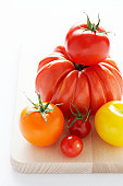 Assorted tomatoes on wooden chopping board