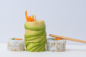 Close up side view of some assorted vegan sushi on white background
