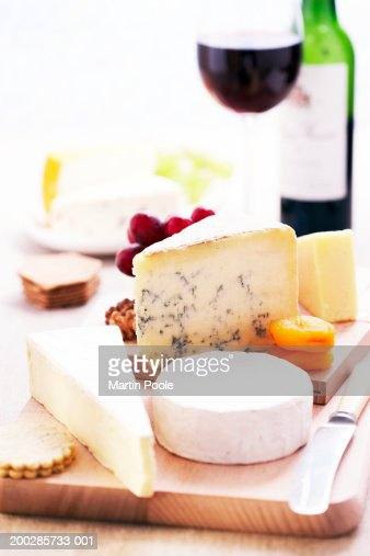 Assortment of cheeses and knife on wooden cheese board, close-up, glass and bottle of red wine in background : Stock Photo