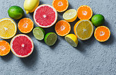 Assortment of citrus fruits on a grey background, top view. Oranges, grapefruit, tangerine, lime, lemon - organic fruits, vegetarian healthy food concept. Flat lay, copy space