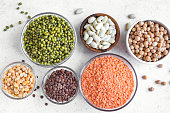 Healthy food, dieting, nutrition concept, vegan protein source. Assortment of colorful legumes in bowls, lentils,  kidney beans, chickpeas, mung, peas on white background, top view, copy space.