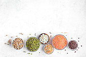 Assortment of colorful legumes in bowls, lentils,  kidney beans, chickpeas, mung, peas on white background, top view, copy space. Healthy food, dieting, nutrition concept, vegan protein source.