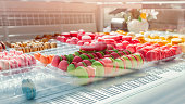 Assortment of colorful macaroons on cafe showcase. Variety of macaron flavours. Sweet almond cakes in store. French sweet biscuits.