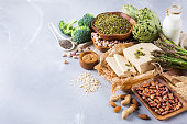 Assortment of healthy vegan protein source and body building food. Tofu soy milk beans asparagus broccoli artichokes almond peanut pumpkin chia flax seeds quinoa oat meal. Copy space background