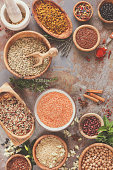 Various types of grains, rice, legumes spices and herbs  in bowls on rustic table, top view