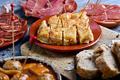 closeup of some plates with an assortment of different spanish cold meats, such as serrano ham, chorizo or cured pork tenderloin, a spanish omelette and meatballs with cuttlefish, on a table