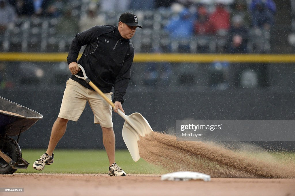 Asst. Groundskeeper Jason Garner throws down a premium field conditioner to dry out the wet spots on the infield during the Colorado Rockies New York Yankees game May 9, 2013 at Coors Field.