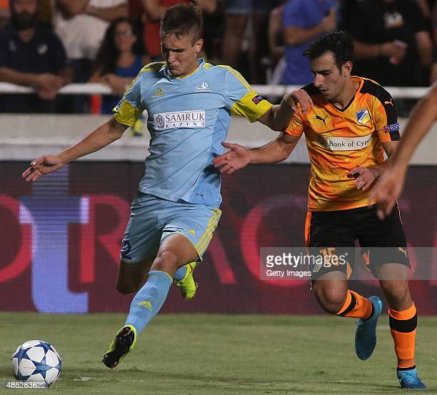 Astana's Baurzhan Dzholchiyev and Apoel's Marios Antoniades in action during UEFA Champions League play off between APOEL Nicosia and FC Astana at...