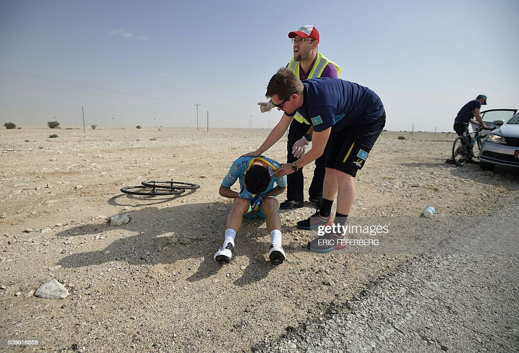 Astana's Kazak Dias Omirzakov is assisted after falling during the first stage of the 2016 Tour of Qatar, between Dukhan and Al Khor Corniche on February 8, 2016. Britain's Mark Cavendish, the former world road race champion, took the gold jersey and covered the 175 kilometres from Dukhan to the Al Khor corniche, north of the capital Doha, in 3hrs 28.31secs, eight seconds in front of Modolo and 11 seconds ahead of Guardini. / AFP / ERIC FEFERBERG