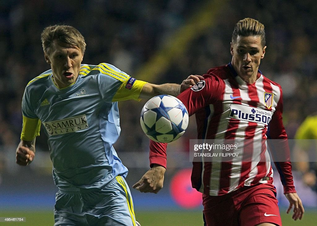 Astana's Kazakh defender Evgeni Postnikov vies for the ball with Atletico Madrid's forward Fernando Torres during the UEFA Champions League group C...