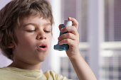 Boy using asthma inhaler to treat inflammatory disease, wheezing, coughing, chest tightness and shortness of breath. Allergy treating concept. Selective focus on inhaler.
