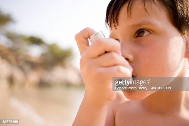 Asthmatic boy (6-7) using inhaler