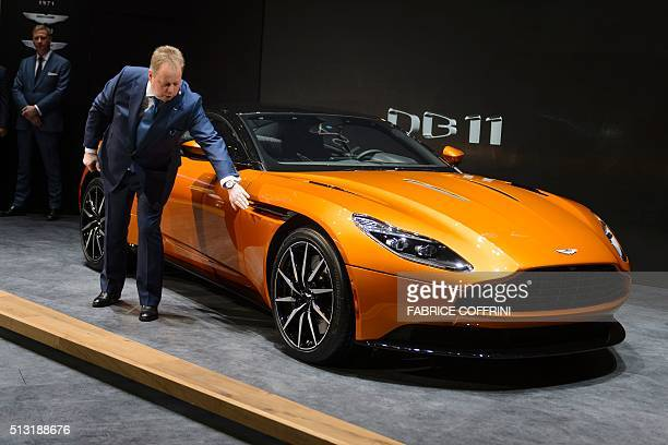 Aston Martin CEO Andy Palmer shows the new DB11 model car at the stand of the British carmaker during the press day of the Geneva Motor Show on March...