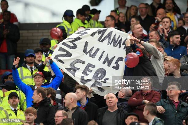 Aston Villa fans with a banner reading '4 managers 3 wins 2 ceos' in the stands