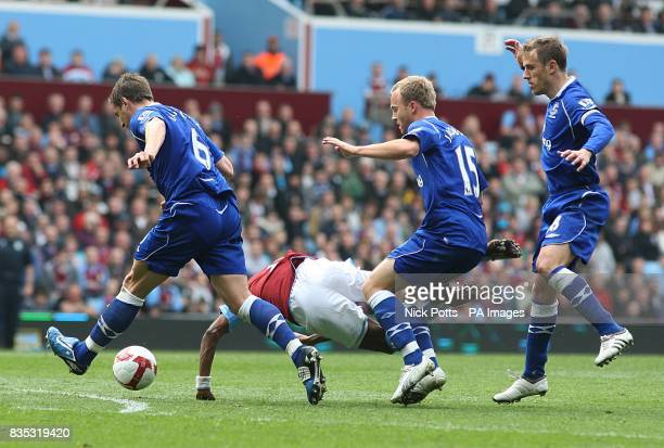 Aston Villa's Ashley Young goes down as he is challenged by Everton's Phil Jagielka Lars Christian Jacobsen and Phil Neville