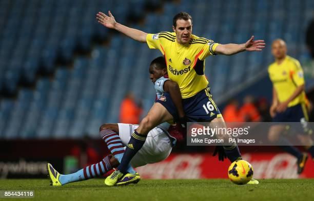 Aston Villa's Christian Benteke and Sunderland's John O'Shea during the Barclays Premier League match at Villa Park Birmingham