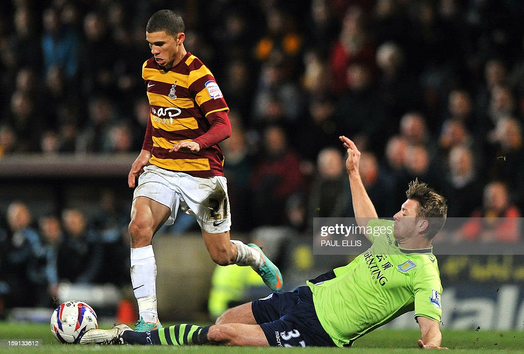 """Aston Villa's English defender Nathan Baker (R) tackles Bradford City's Bermudian forward Nahki Wells during the English League Cup first leg semi-final football match between Bradford City and Aston Villa at The Coral Windows Stadium in Bradford, England, on January 8, 2013. Bradford won the match 3-1. USE. No use with unauthorized audio, video, data, fixture lists, club/league logos or """"live"""" services. Online in-match use limited to 45 images, no video emulation. No use in betting, games or single club/league/player publications."""