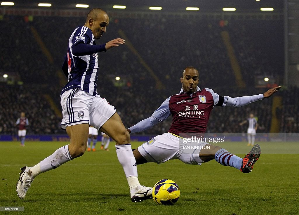 """Aston Villa's English midfielder Fabian Delph (R) tackles West Bromwich Albion's Nigerian striker Peter Odemwingie during the English Premier League football match between West Bromwich Albion and Aston Villa at The Hawthorns in West Bromwich on January 19, 2013. AFP PHOTO/Ian KINGTON - RESTRICTED TO EDITORIAL USE. No use with unauthorized audio, video, data, fixture lists, club/league logos or """"live"""" services. Online in-match use limited to 45 images, no video emulation. No use in betting, games or single club/league/player publications."""