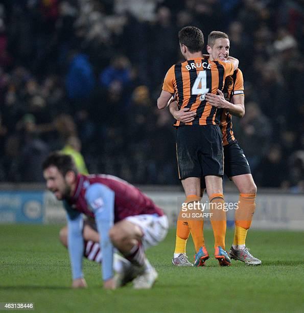 Aston Villa's English midfielder Joe Cole rests as Hull City's Northern Irish defender Alex Bruce and Hull City's English defender Michael Dawson at...