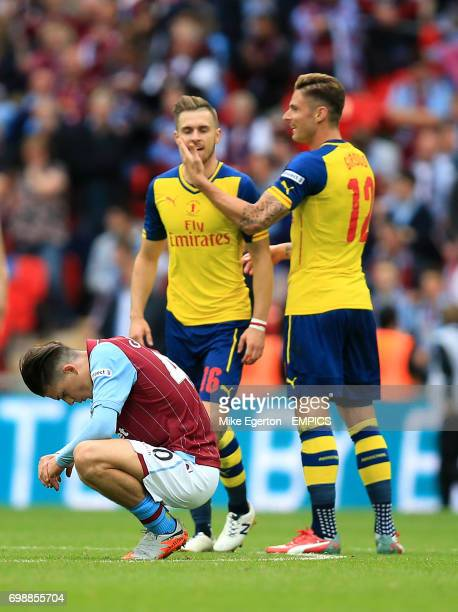 Aston Villa's Jack Grealish is dejected at the final whistle as Arsenal's Aaron Ramsey and Olivier Giroud celebrate