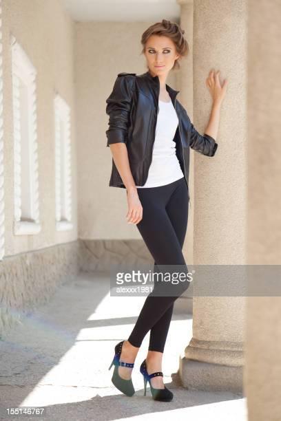 Astonishing fashion young woman posing playfully near massive columns outdoors
