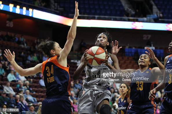Astou Ndour of the San Antonio Stars drives to the basket challenged by Kelly Faris and Morgan Tuck of the Connecticut Sun during the San Antonio...
