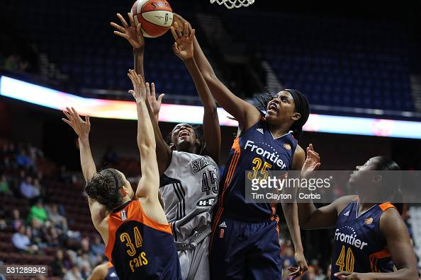 Astou Ndour of the San Antonio Stars drives to the basket challenged by Kelly Faris and Jonquel Jones of the Connecticut Sun during the San Antonio...
