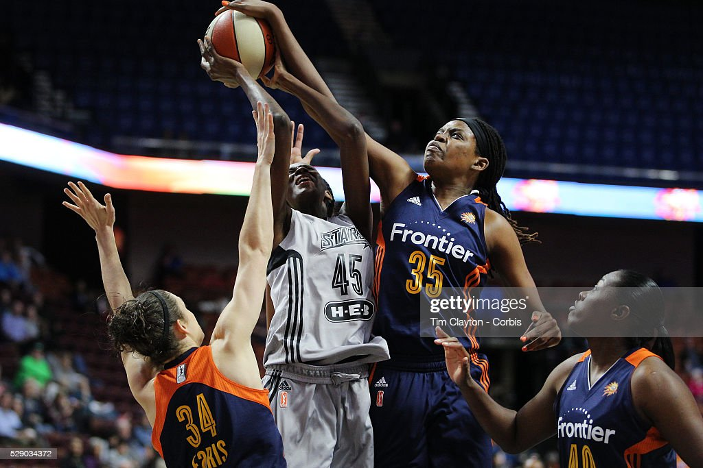 Astou Ndour of the San Antonio Stars is fouled as she drives to the basket by Kelly Faris of the Connecticut Sun as Jonquel Jones of the Connecticut...