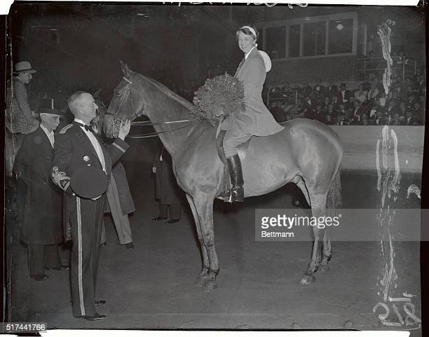 Astride her mount 'Banger' Mrs Franklin D Roosevelt wife of the President is pictured after she had been presented with a huge floral bouquet during...
