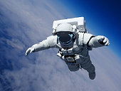 Astronaut in space above the clouds of the Earth..