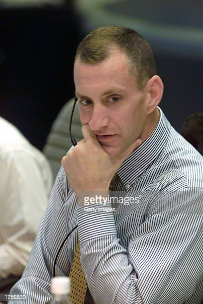 Astronaut Charles O Hobaugh spacecraft communicator stands at his console in the shuttle flight control room in in Houston's Mission Control Center...