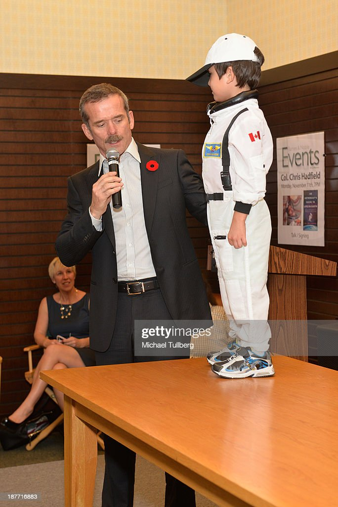 Astronaut Colonel <a gi-track='captionPersonalityLinkClicked' href=/galleries/search?phrase=Chris+Hadfield&family=editorial&specificpeople=2700911 ng-click='$event.stopPropagation()'>Chris Hadfield</a> appears with a guest at a signing for his book 'An Astronaut's Guide To Life On Earth' at Barnes & Noble bookstore at The Grove on November 11, 2013 in Los Angeles, California.