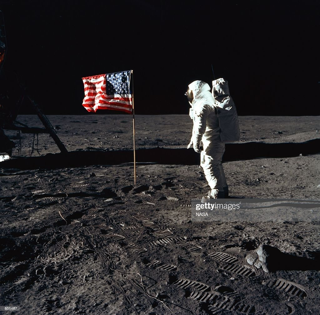 Astronaut Edwin E Aldrin Jr the lunar module pilot of the first lunar landing mission stands next to a United States flag July 20 1969 during an...