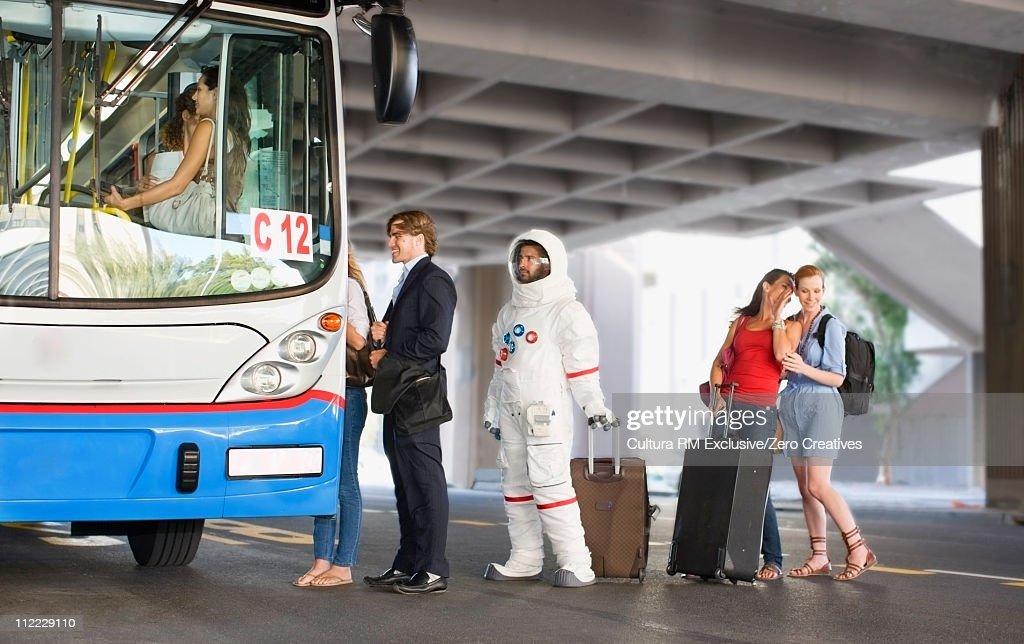 Astronaut entering a bus : Stock Photo