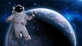 Astronaut in space giving thumbs up, cosmonaut floating above planet Earth, 3D rendering