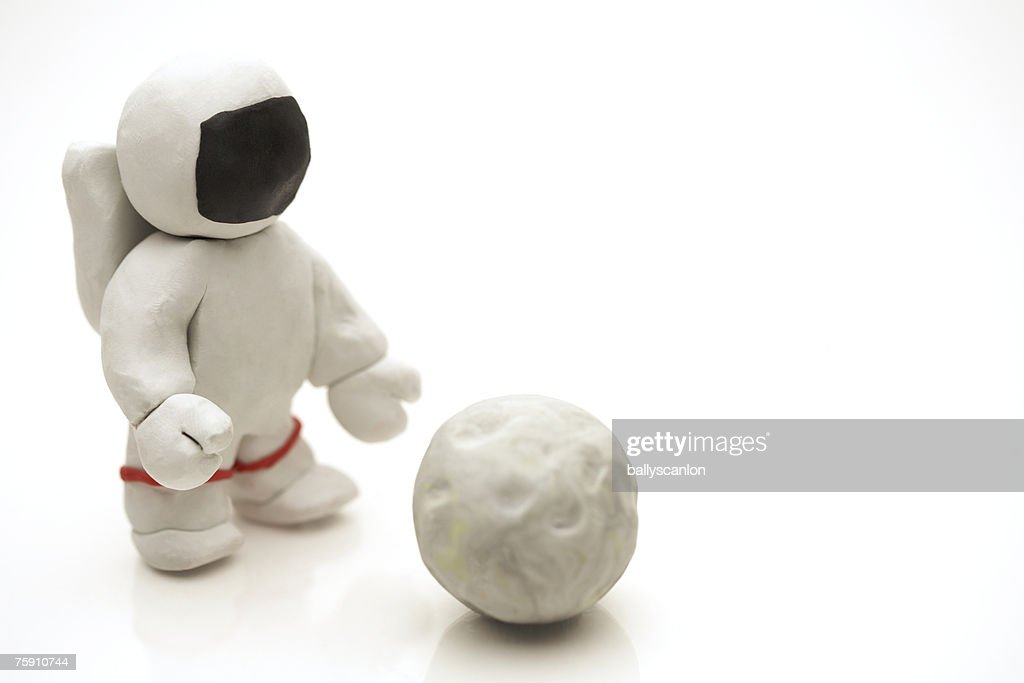 Astronaut made of clay reaching for the moon : Stock Photo