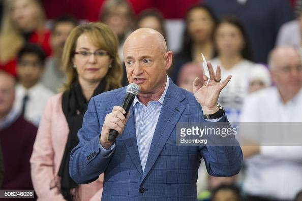 Astronaut Mark Kelly center speaks as his wife Gabrielle Giffords former US Representative from Arizona left listens during a campaign event for...