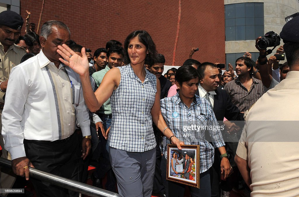 US astronaut of Indian-Slovenian origin Sunita Williams (C) waves as she leaves after receiving an honourary doctorate degree, 'Doctor of Philosophy' by Vice-Chancellor of Gujarat Technological University, Akshai Aggarwal during her visit to the institution on the outskirts of Ahmedabad on April 6, 2013. Williams holds a world record for total cumulative spacewalk time by a female astronaut and has spent a total of 322 days in space on two missions. AFP PHOTO / Sam PANTHAKY