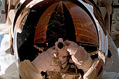 Expedition 14 flight engineer Suni Williams uses a digital still camera to expose a photo of her helmet visor during a February 2007 spacewalk. Also visible in the reflections in the visor is a solar