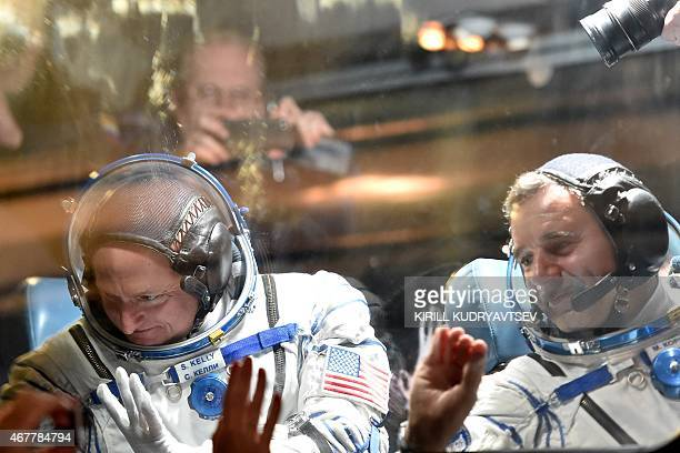 US astronaut Scott Kelly and Russian cosmonaut Mikhail Kornienko wave from a bus after their space suits were tested at the Russianleased Baikonur...