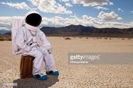 宇宙飛行士に座るスーツケースの砂漠